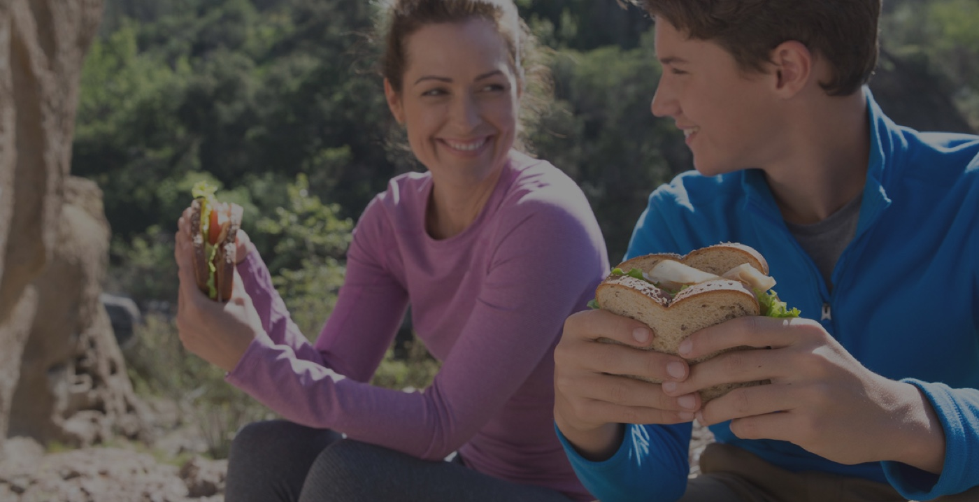 Mom and son eating sandwich on a hike image